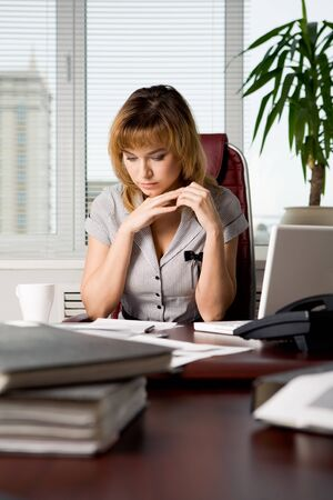 Photo of attractive woman sitting at workplace in the office and reading document photo