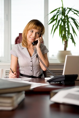 secretary office: Busy secretary speaking on the phone in the office