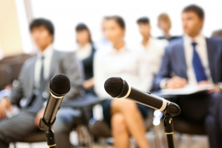 audiences: Image of two microphones on background of people listening to lecture at conference