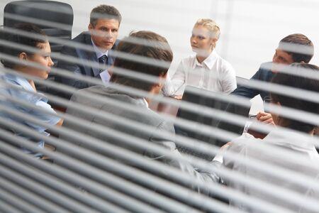 espalda: Ver detr�s de persiana veneciana de associates interactuar en reuni�n de trabajo