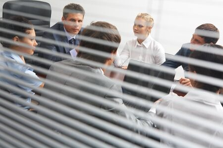 listening back: View from behind venetian blind of associates interacting at working meeting
