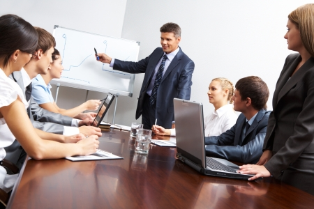Image of smart business people looking at their leader while he explaining something on whiteboard during seminar photo