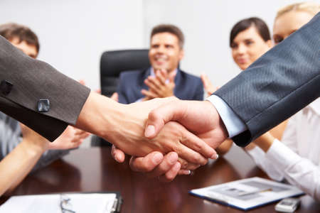 Photo of successful business partners handshaking after striking great deal with applauding people at background photo