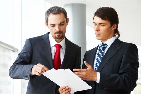 Image of confident businessman looking at document in partner's hand while discussing it photo