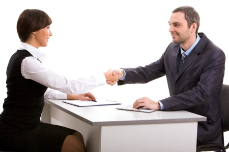 Photo of businesspartners shaking hands after making an agreement and looking at each other photo