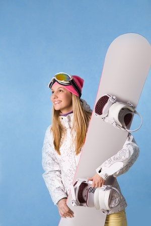 Portrait of healthy woman with pair of skis in hands looking aside and smiling photo