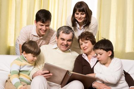 Retrato de senior y jóvenes parejas con sus hijos mirando fotos de familia