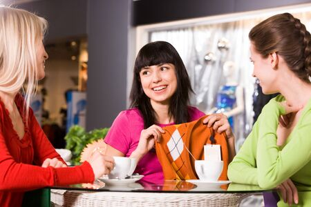 Photo of happy girl showing fashionable pullover to her friends in cafe photo