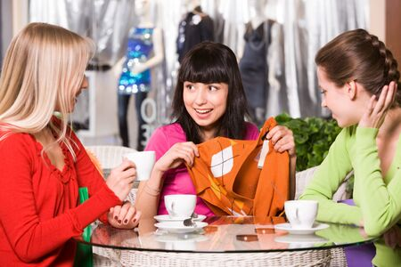 Photo of happy girl showing fashionable pullover to her friends in cafe Stock Photo - 9163454