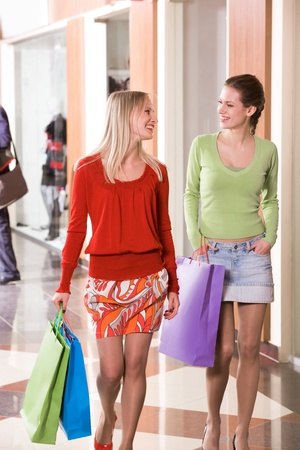 go inside: Photo of happy girls walking down trade center and chatting Stock Photo