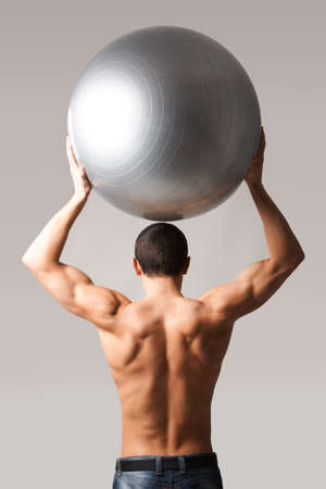 Back view of shirtless man in jeans holding big ball above head photo