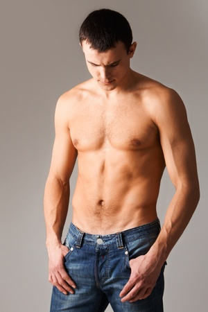 Image of shirtless man in jeans isolated over grey background photo