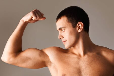 musculo: Imagen de hombre poderoso mirando sus m�sculos durante el ejercicio