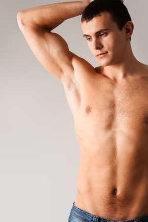 expresion corporal: Imagen de un hombre sin camisa en jeans aisladas sobre fondo gris