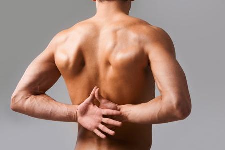 espalda: Vista posterior del hombre sin camisa manteniendo sus manos tras la espalda