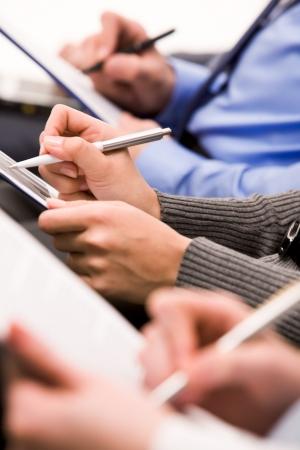 conferentie: Close-up van menselijke handen met pennen over zakelijke documenten