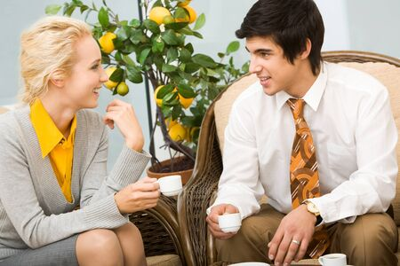Portrait of smart colleagues having conversation in office during coffee break photo