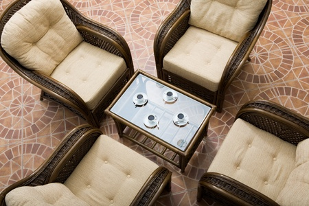 Above view of glass table surrounded by four brown arm chairs  photo