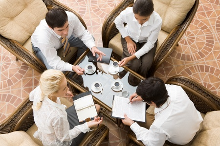 coffee meeting: View from above of four businesspeople discussing work