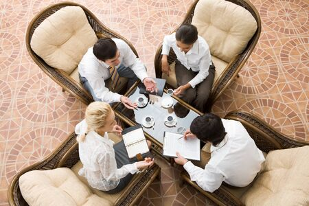 planning strategy: View from above of four businesspeople discussing work