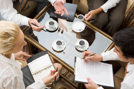 coffee meeting: Above view of confident businesspeople planning work in the room  Stock Photo