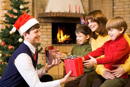 fireplace family: Portrait of happy family celebrating Christmas at home