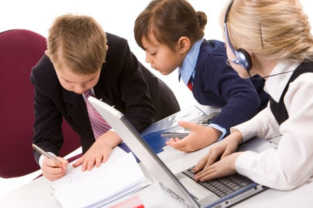Photo of smart girl looking at serious boss writing on paper in working environment photo