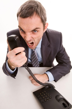 stressed businessman: Image of aggressive boss yelling into telephone receiver over white background