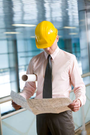 Portrait of confident foreman in helmet learning blueprint photo