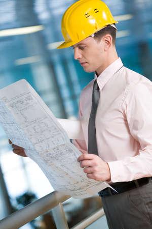 Portrait of confident foreman in helmet learning blueprint photo