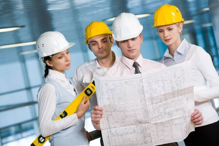 Portrait of confident architects in helmets learning blueprint photo