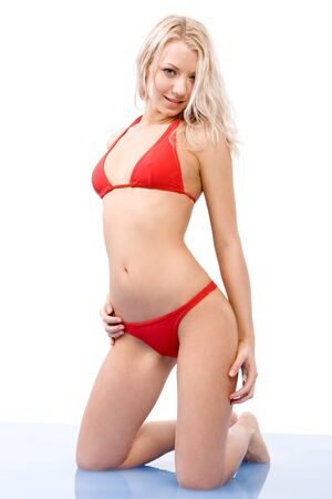 Portrait of blond female in red bikini looking at camera while in water photo