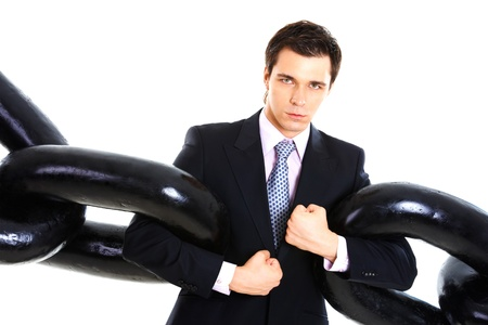 Portrait of powerful businessman with several sections of huge chain over white background photo