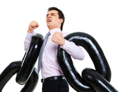Portrait of tense businessman with two sections of huge chain showing that it is heavy photo