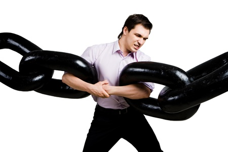 metaphor: Portrait of tense businessman with two sections of huge chain over white background