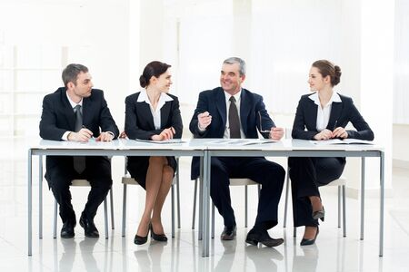 sitting at table: Portrait of business people looking at older man speaking something  Stock Photo