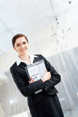 Portrait of smart secretary with smile holding folder in hands  photo