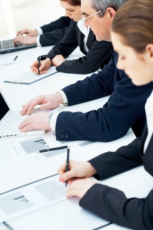 executive courses: Vertical image of close-up of people hands during work in line