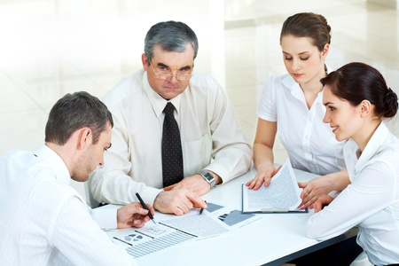 Photo of confident co-workers gathered together and brainstorming photo