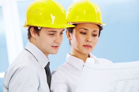Portrait of two architects in helmets looking document at meeting Stock Photo - 9163480