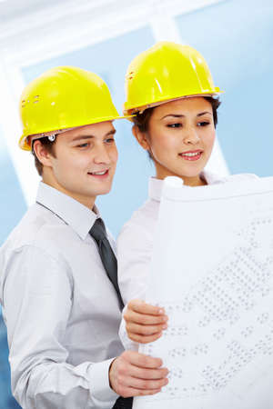 Portrait of two architects in helmets looking document at meeting Stock Photo - 9163481