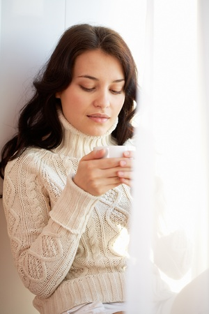 Portrait of charming girl in sweater holding cup and looking at it photo