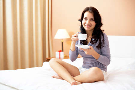 Portrait of brunette with cup of tea sitting on bed and looking at camera photo