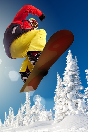 snowboarder jumping: Portrait of boy with snowboard jumping near snowy forest  Stock Photo