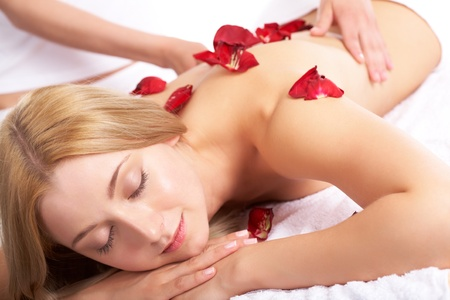 Portrait of calm female during luxurious procedure of massage with rose petals photo