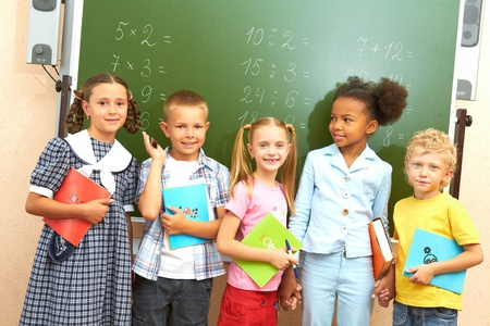 racial diversity: Portrait of several kids standing by blackboard in classroom