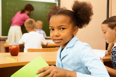 foreground: Portrait of cute girl looking at camera at workplace during lesson
