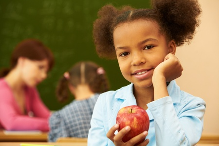 Portrait of cute girl with apple looking at camera during lesson photo