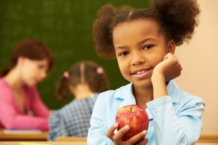 educadores: Retrato de una chica linda con apple mirando la c�mara durante la lecci�n