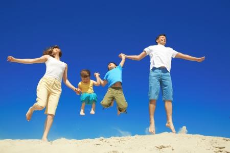 familia feliz: Familia alegre saltar juntos durante vacaciones    Foto de archivo